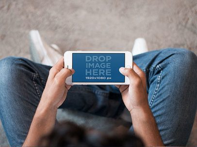 Top View of a Teen Sitting and Playing with his iPhone 7 Plus in Landscape Position Mockup 13044
