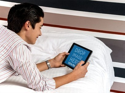 Teen Boy Playing on his iPad Mini Mockup in Landscape View in his Room 13053a