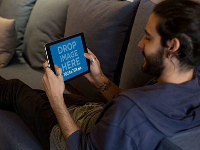 iPad Mockup in Landscape Position of a Man Lying on a Sofa at Home 13105