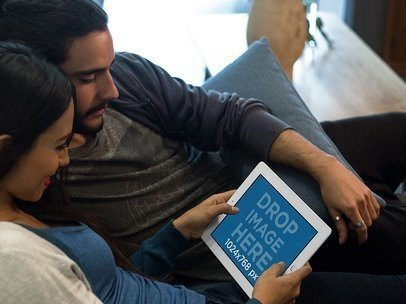 White iPad Mockup in Landscape Position of a Couple Lying on a Couch in their Apartment a13103