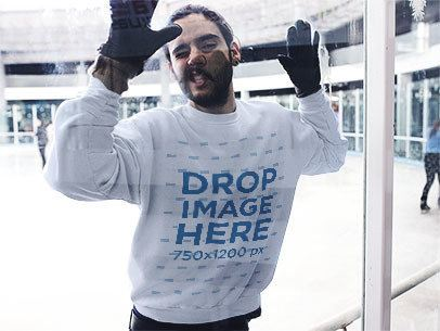 Funny Guy Against a Glass Wearing a Crewneck Sweatshirt at an Ice Skating Rink a13256