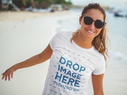 Smiling Lovely Woman Wearing a T-Shirt Mockup and Sunglasses at the Beach a12725