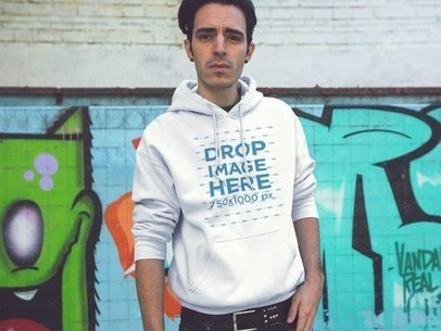 Hoodie Mockup of a Young Man Standing Near a Graffiti Wall a12836