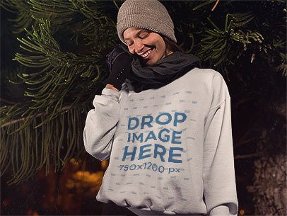 Young Woman Wearing a Beanie and Crewneck Mockup Near the Pine Trees a13243