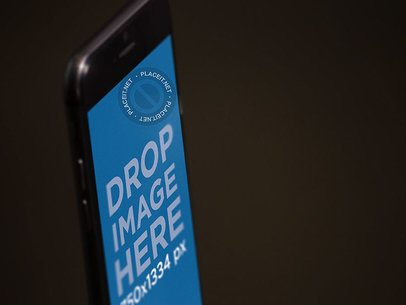 Angled Close Up Shot Mockup of a Black iPhone Standing in Portrait Position a12711
