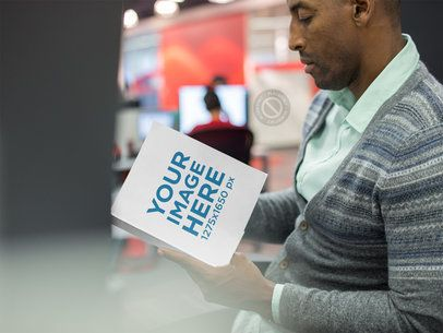 Serious Black Man Reading a Book While at the Office Mockup a14501