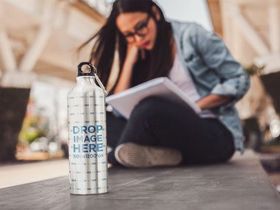 Girl Sitting Down Reading With an Aluminum Water Mockup Bottle Near Her a14886