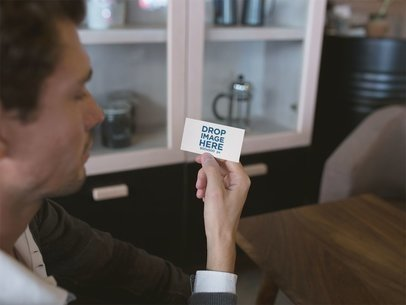 Young Man Holding a Business Card Template in a Coffee Shop a15003