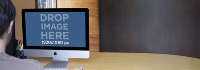 Mockup Template of a Young Man Working on an iMac