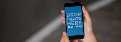 iPhone Mockup Being Held in Front of a Black Background a9334