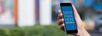 Black iPhone 6 Mockup Template Being Held Outdoors a10035